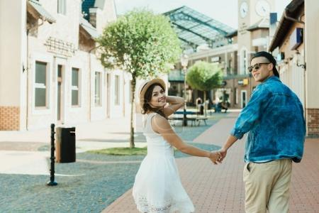 Photo for Smiling trendy couple holding hands while walking in city - Royalty Free Image