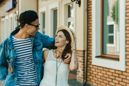 Photo for Happy young hipster couple hugging while walking on the street - Royalty Free Image