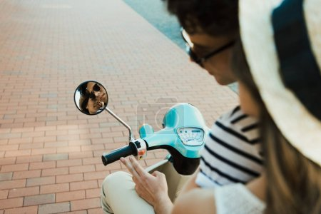 Photo pour Recadrée tir du jeune couple scooter d'équitation et de regarder le reflet dans le miroir - image libre de droit