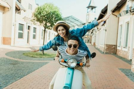 Photo for Happy stylish young couple riding scooter  and smiling at camera - Royalty Free Image