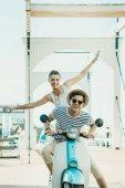couple riding retro scooter