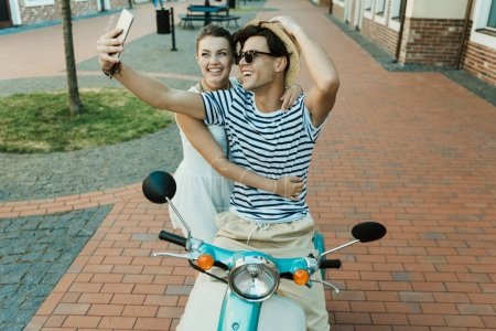Photo for Smiling young couple taking selfie on smartphone while sitting on scooter outdoors - Royalty Free Image