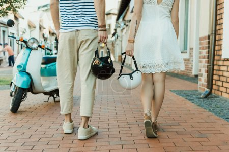 Photo for Cropped shot of casual couple holding helmets while walking together outdoors - Royalty Free Image