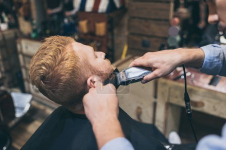 barber trimming customers beard