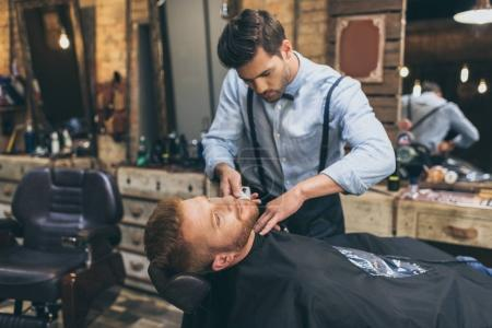 Photo pour Homme barbe tondeuse clients barbe dans le salon de coiffure - image libre de droit