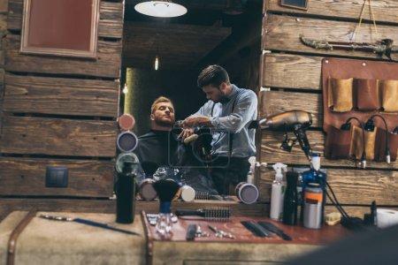 Barber trimming customers beard