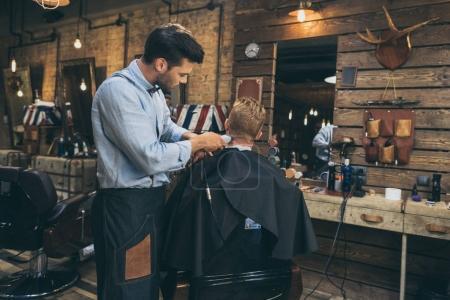 Photo pour Homme coiffeur coupe les cheveux du client dans le salon de coiffure - image libre de droit