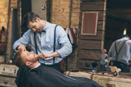 Photo for Male barber trimming customers beard in barber shop - Royalty Free Image