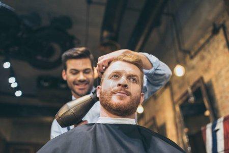 Photo pour Jeune coiffeur séchant les cheveux du client avec sèche-cheveux dans le salon de coiffure - image libre de droit