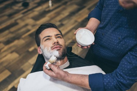 Photo for Barber applying foam before shaving of customer in barber shop - Royalty Free Image