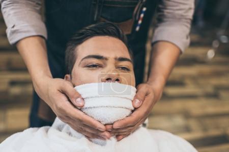 Foto de Cliente con una toalla caliente en la cara antes de afeitar en la peluquería - Imagen libre de derechos