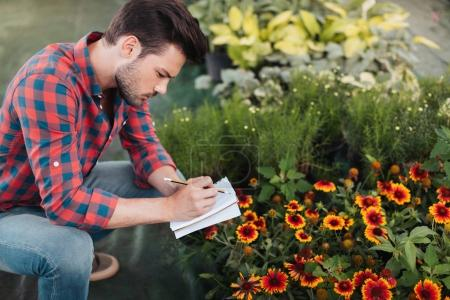 gardener making notes in notebook