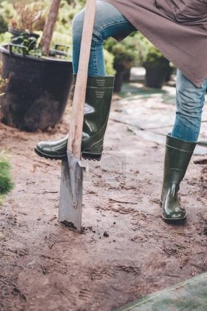 gardener in rubber boots with spade
