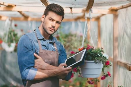 gardener with tablet in greenhouse