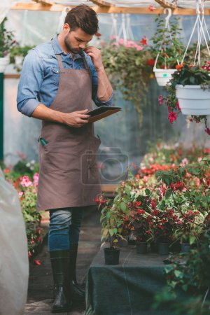 Gardener in apron with tablet