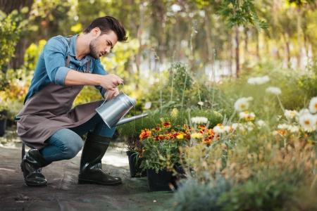 Photo for Side view of young gardener in apron and rubber boots with watering can in hand watering plants in garden - Royalty Free Image