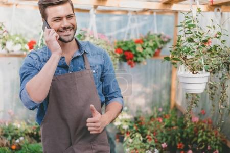 gardener talking on smartphone in greenhouse