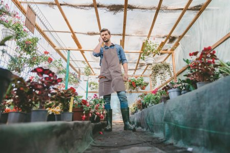 Gardener talking on smartphone in greenhouse