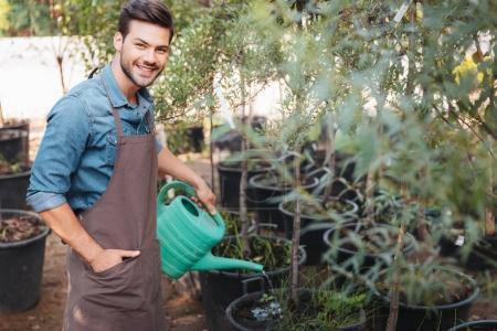 Photo pour Portrait de jardinier souriant dans un tablier avec arrosoir arrosage de plantes dans le jardin - image libre de droit