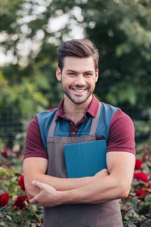 Photo pour Portrait de jardinier souriant dans tablier tenant tablette numérique dans les mains tout en se tenant debout dans le jardin - image libre de droit