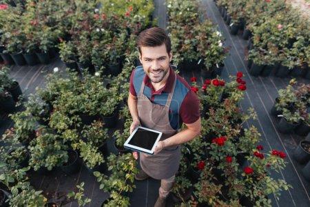 Photo pour Vue d'angle élevé de jardinier en souriant dans le tablier avec tablette de travail dans le jardin - image libre de droit