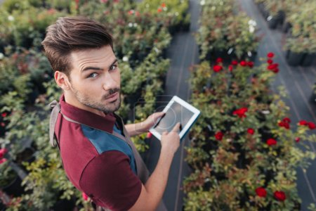 gardener with tablet during work in garden