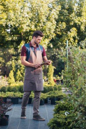 Gardener with tablet during work in garden