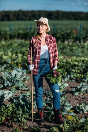 Photo for Beautiful young farmer holding fresh beetroots and hoe while smiling at camera on field - Royalty Free Image