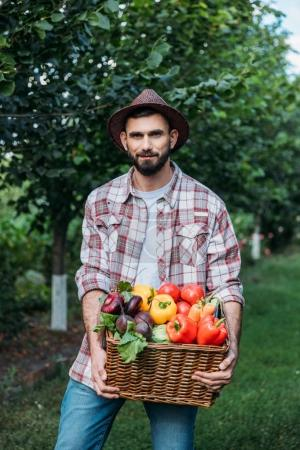 Photo for Handsome bearded farmer holding basket with fresh organic vegetables - Royalty Free Image