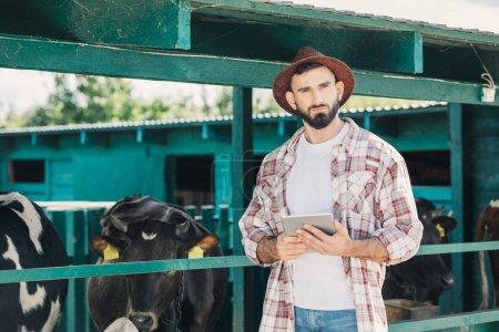 Foto de Apuesto granjero barbudo sosteniendo la tableta digital y mirando a cámara mientras trabajaba en el establo - Imagen libre de derechos