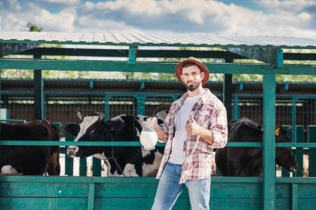 Photo for Smiling bearded farmer holding glass jug with milk and showing thumb up at stall - Royalty Free Image