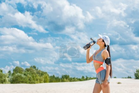 Photo for Asian sportswoman with sport armband for smartphone drinking water from sport bottle - Royalty Free Image
