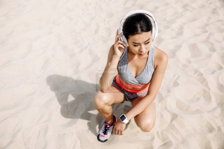 Photo for Beautiful asian sportswoman with headphones listening music - Royalty Free Image