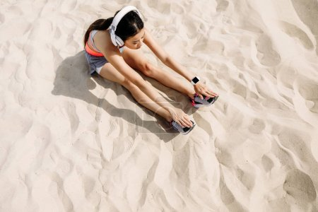 sportswoman stretching on sand