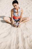 sportswoman stretching on sand