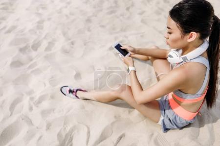 sportswoman with smartphone and headphones