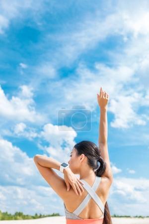 Photo pour Vue arrière de la sportive asiatique avec montre intelligente debout contre ciel nuageux - image libre de droit