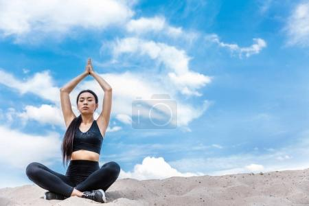 Woman meditating in lotus yoga pose