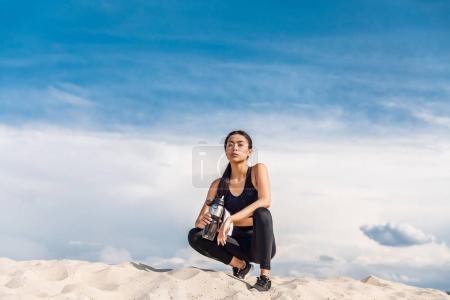 Photo pour Fatigué asiatique sportif avec sport bouteille reposant sur le sable contre ciel nuageux - image libre de droit