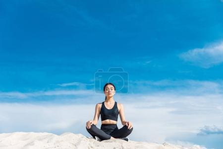 Photo pour Asiatique femme méditant dans lotus yoga pose sur sable contre ciel nuageux - image libre de droit