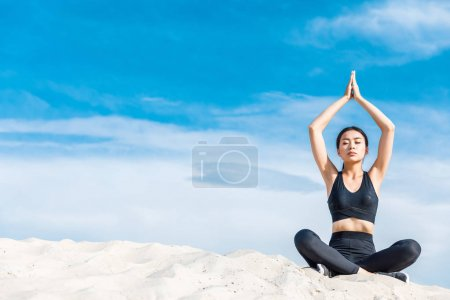 Photo pour Asiatique femme méditant dans lotus yoga pose avec mudra namaste sur sable contre ciel nuageux - image libre de droit