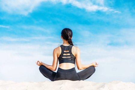 Photo pour Vue arrière du femme méditant dans lotus yoga pose sur sable contre ciel nuageux - image libre de droit