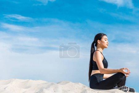 Asian woman meditating in lotus pose