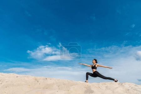 Photo pour Asiatique femme pratiquant yoga en guerrier pose contre ciel nuageux - image libre de droit