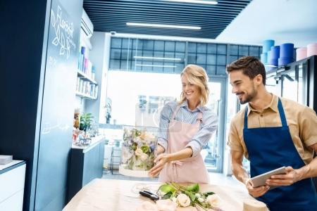 florists with digital tablet in flower shop