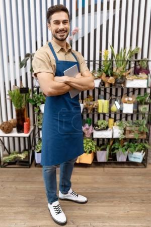 Foto de Guapo joven florista en delantal que tableta digital y sonriendo a la cámara en la tienda de la flor - Imagen libre de derechos