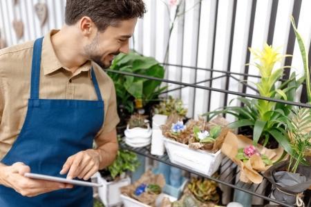 Photo pour Beau jeune fleuriste souriant utilisant une tablette numérique tout en travaillant dans un magasin de fleurs - image libre de droit