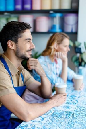 Foto de Vista lateral de los trabajadores jóvenes en delantales tomando café y mirando lejos - Imagen libre de derechos