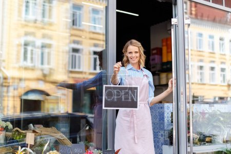 Photo for Attractive young female florist in apron holding open sign and smiling at camera - Royalty Free Image