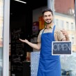 Small business owner holding open sign and smiling...